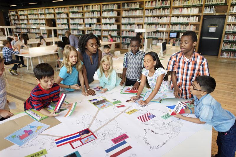 Students gathered around an atlas