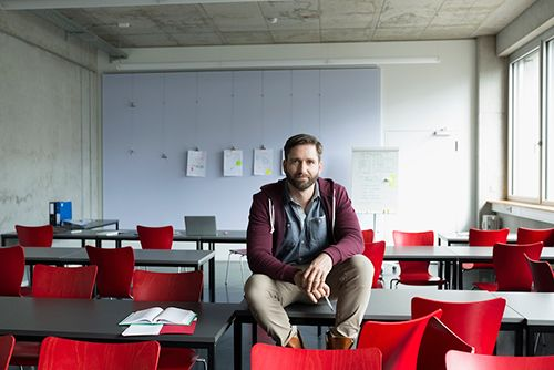Educator sitting on desk in an empty classroom