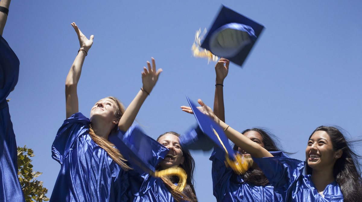 Excited graduates throwing caps into the air