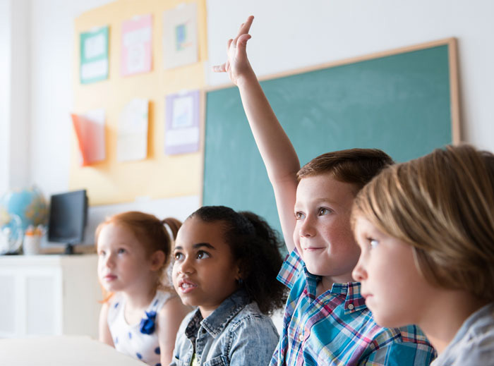 Kids in math classroom raising hands