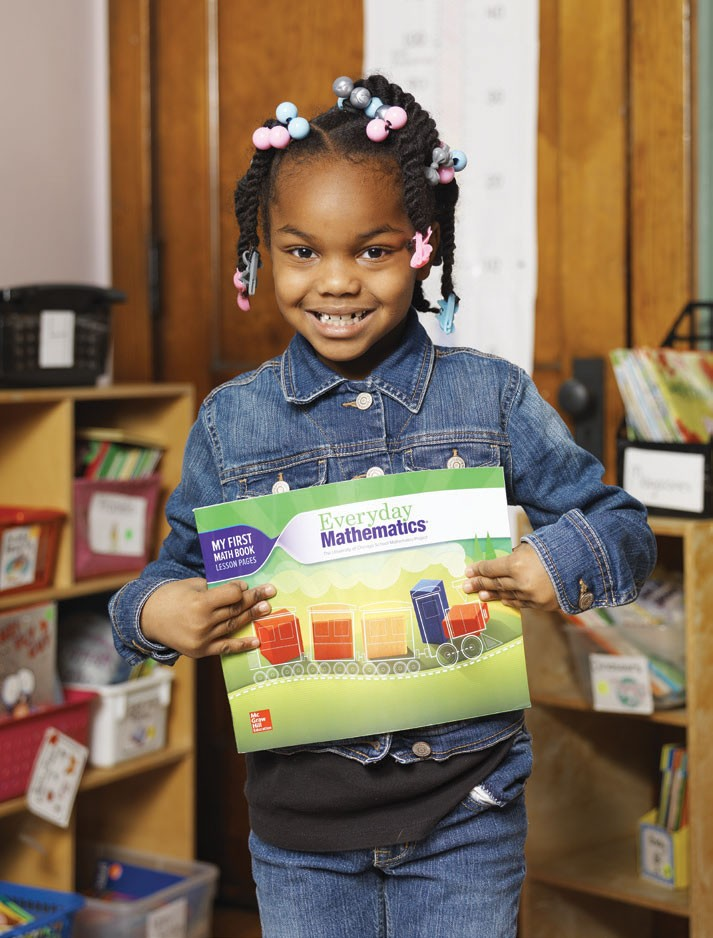 Young girl holding Everyday Math lesson book